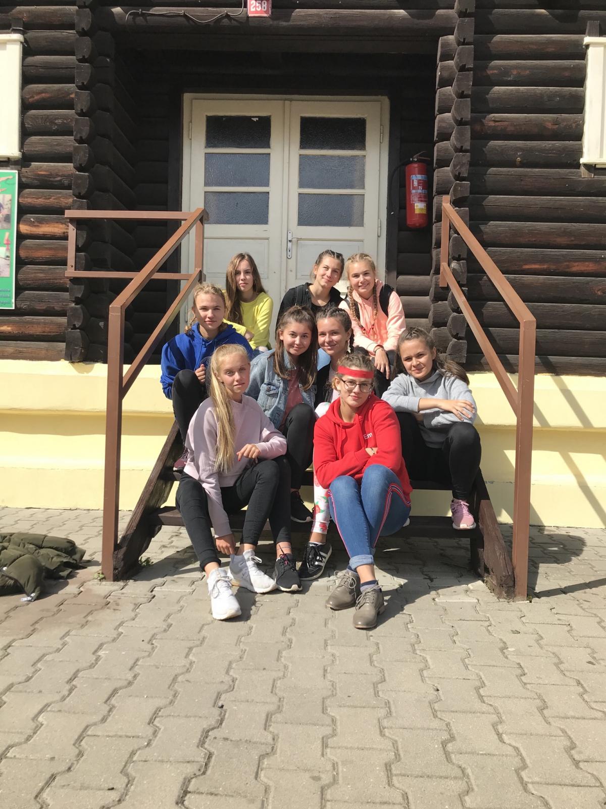 Adaptační pobyt Zbraslavice: dívky sedí na dřevěných schodech