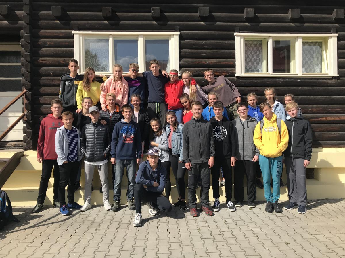Adaptační pobyt Zbraslavice:  žáci stojí před dřevěnou budovou