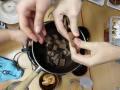 lámání čokolády nad miskou plnou částí mandarinky
